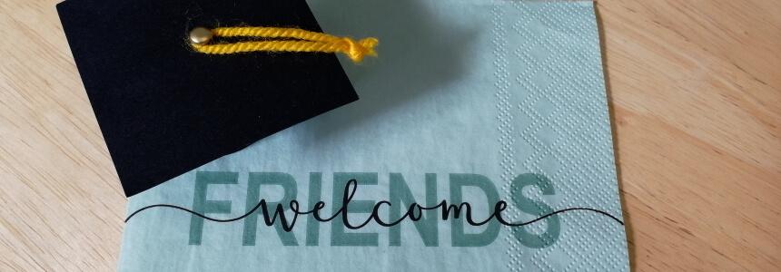 Begrüßung zur Promotionsfeier - Doktorhut und der Schriftzug Friends welcome