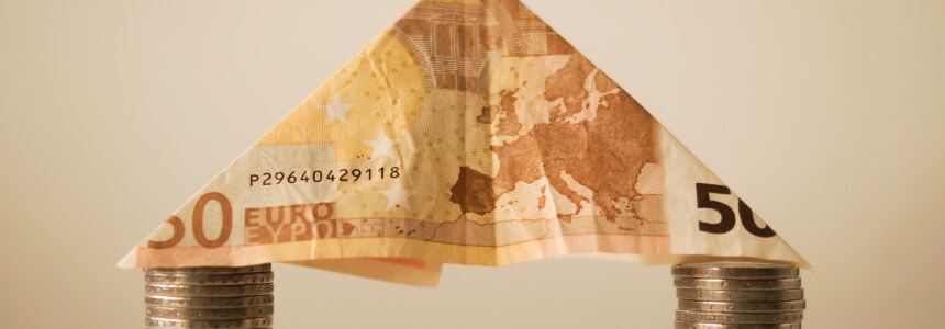 Geldgeschenke - dreieckig gefalteter 50-Euro-Schein, der auf Münzen steht.
