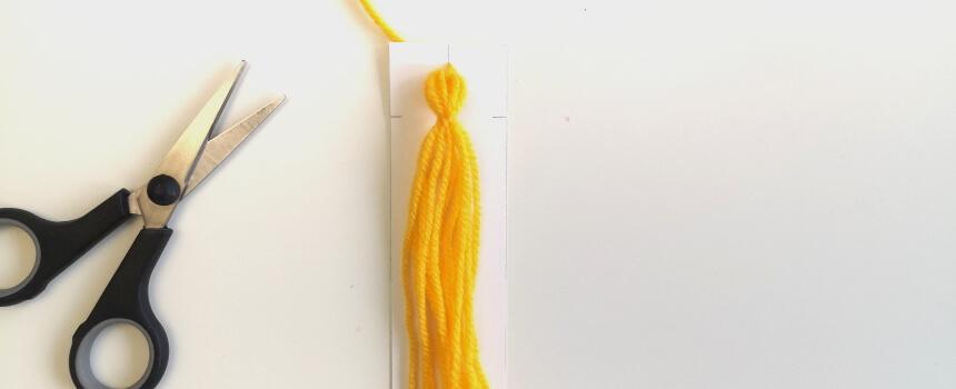 Kurze Enden der Wolle am Knoten abschneiden.