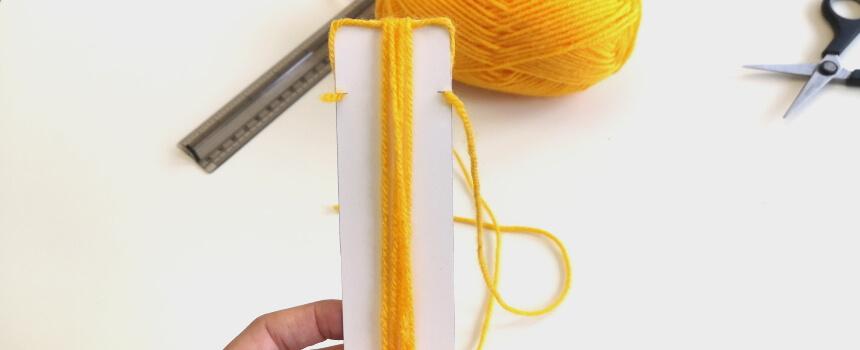 Mit Wolle das Pappstück umwickeln.